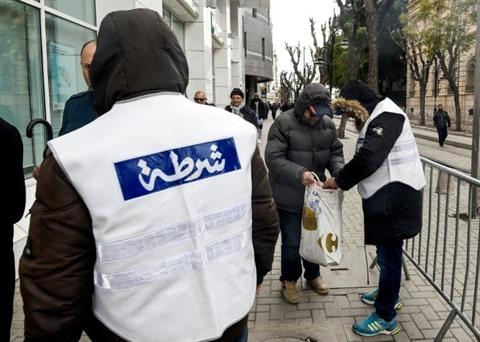 Des policiers inspectent les sacs de passants, le 14 janvier à Tunis.   Photo : AFP/VNA/CVN