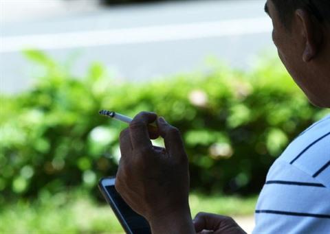 Un homme fume une cigarette en regardant son smartphone, le 198 mai à Manille, aux Philippines. Photo : AFP/VNA/CVN
