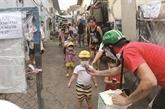 Un volontaire Français distribue des paniers-repas aux plus démunis