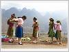Des femmes d'ethnies minoritaires mettent de nouvelles robes avant d'entrer au marché.