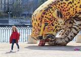 Une fille passe devant une œuvre d'art pneumatique en forme d'un jaguar buvant de l'eau sur l'Île Rousseau, à Genève, en Suisse, le 22 mars 2017. Photo : Xinhua/VNA/CVN
