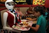 Une jeune cliente prend un plateau apporté par un robot le 4 juillet dans une pizzeria à Multan, où premier restaurant du pays où les serveuses sont des robots. Photo : AFP/VNA/CVN
