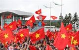 Des milliers de Vietnamiens, portant le drapeau rouge à étoile d'or, accueillent le Onze vietnamien U23, le 28 janvier à Hanoï. Photo : Quôc Khanh