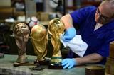 Des répliques de la Coupe du monde soigneusement nettoyés et restaurés par un artisan dans les ateliers Bertoni, le 11 avril à Paderno Dugnano. Photo: AFP/VNA/CVN