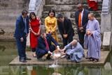 L'ambassadeur des États-Unis au Vietnam, Daniel J. Kritenbrink (assis), relâche des carpes à la pagode de Kim Liên, à Hanoï, faire ses adieux aux Génies du Foyer.