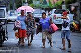 Des gens se déplacent sous la pluie apportée par le typhon Molave à Manille le 25 octobre. Photo : AFP/VNA/CVN