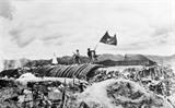 Des troupes du <em>Viêt minh</em> plantant leur drapeau sur le QG du général français de Castries, commandant du camp retranché de Diên Biên Phu, le 7 mai 1954.<br /> Photo : Archives/VNA/CVN