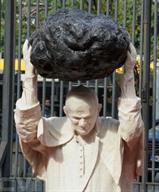 La sculpture de l'artiste Jerzy Kalina représentant Saint Jean Paul II en train de soulever une grande météorite, posée à l'entrée du Musée national de Varsovie, le 24 septembre lors de son inauguration.<br /> Photo : AFP/VNA/CVN