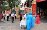 Des électeurs de Hanoï qui se rendent le 23 mai aux urnes font vérifier leur température corporelle et font la queue pour garder leurs distances dans un bureau de vote. Photo : VNA/CVN